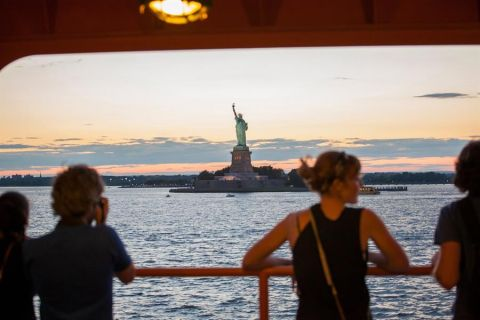 Fotografía cedida este miércoles por NYC & Company donde aparecen unas personas mientras observan la Estatua de la Libertad mientras viajan en un ferri, en Nueva York (Estados Unidos).