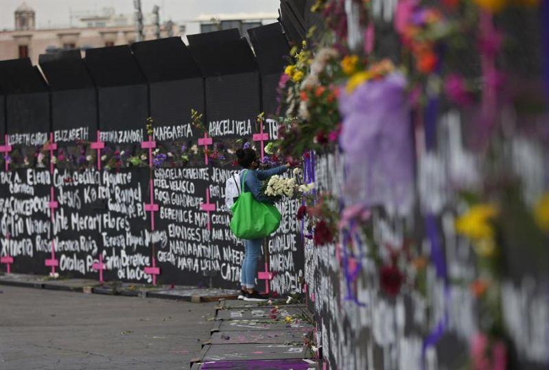 Una mujer coloca flores y carteles con nombres de víctimas por feminicidios en cercos metálicos instalados por el gobierno capitalino en una protesta contra los feminicidios este 7 de marzo de 2021, en Ciudad de México (México).